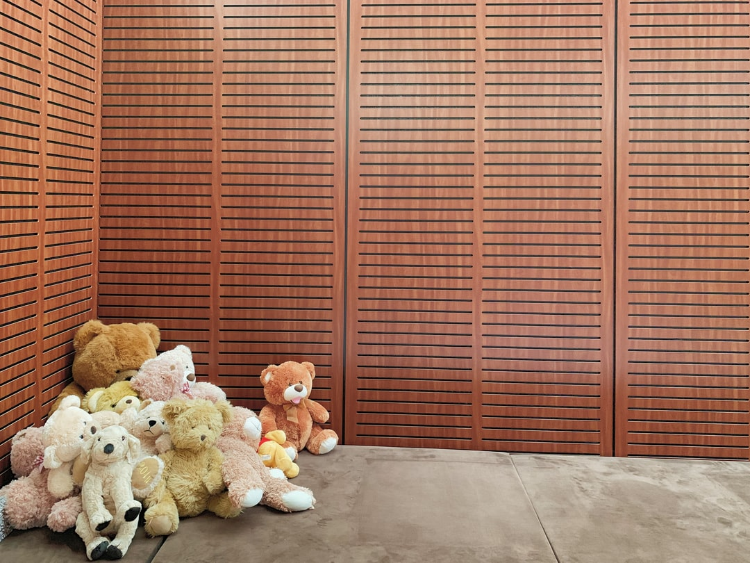 A group of teddy bears sitting next to a window
